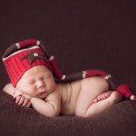 Pictured above is a sleeping newborn baby in a red hat by newborn photographer Lorna Kirkby