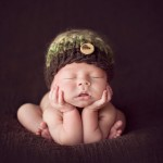 Pictured above is a newborn child leaning on his own hands by newborn photographer Lorna Kirkby