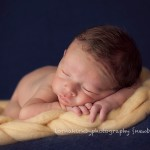 A picture of sleeping newborn baby boy on soft padding as part of Melbourne newborn photography portfolio session.
