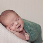 Picture of gorgeous newborn baby in green wrap by Melbourne newborn photographer, Lorna Kirkby.