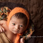 Picture of newborn baby boy in orange hat, Zach portfolio by Melbourne newborn photographer Lorna Kirkby