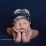Newborn photographic images of Sammy in a classic froggy pose.