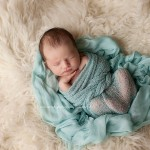 Photo of a newborn girl wrapped in blue flower from the Juliana portfolio in Melbourne newborn photography by Lorna Kirkby.