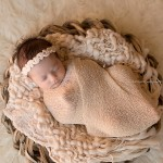 Session photography of a pretty-in-peach newborn girl named Alessia.