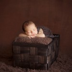 Picture of gorgeous sleeping newborn boy in crate from the Hugo collection by Lorna Kirkby, a Melbourne photographer specializing in baby, child, maternity and newborn photography.