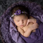 Stunning newborn photography of little girl in purple.