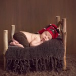 from the Jensen portfolio, custom newborn photography picture of newborn asleep on a small bed.