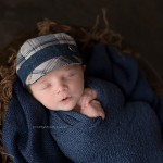 A gorgeous little newborn wearing a blue cap.