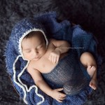 A beautiful newborn dressed in striking blue.