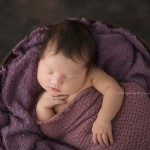 Charlotte poses in royal purple for natural-light, newborn photography.