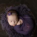 A photograph of Chloe cuddling in royal purple for the beautiful babies portfolio.