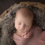 Cute, sleepy newborn girl in studio session.