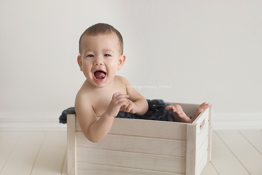 An image of Kaelan laughing in a box for the beautiful babies portfolio.